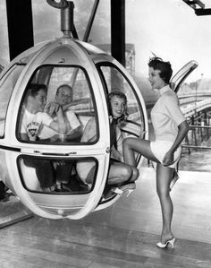 A pair of excited boys join Pacific Ocean Park staff in a Skywayride car, Santa Monica, 1958. POP, which replaced the earlier amusement park at the Ocean Park Pier, closed in 1967. The pier was demolished in 1974 after a series of fires.
