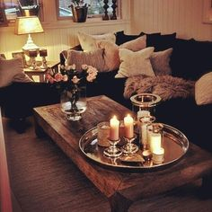 Obsessed with this - wooden table has great texture and anchors the room with textured, luxurious pillows/throw on a dark sofa