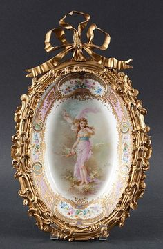 "<b>French Sevres ormolu-mounted painted porcelain plaque</b> <br /> 19th century; signed A. Collott,"" porcelain with central scene of Venus and Cupid and parcel-gilt floral border, Sevres type mark underneath, scroll-form ormolu mounts with large bow, 16 in. L. total"