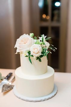 Simple two tier wedding cake topped with flowers and greenery: http://www.stylemepretty.com/new-mexico-weddings/santa-fe-nm/2016/08/23/intimate-santa-fe-destination-wedding/ Photography: Callie Manion - http://www.calliemanionphotography.com/
