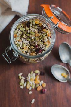 Healthy snack of pumpkin seeds, sunflower seeds, golden raisins, and cranberries.
