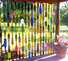 DIY Wine Bottle Fence. Use a diamond drill to make holes in the bottles and thread them on poles. Great idea for a room divider as well.