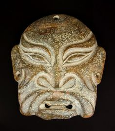 A Chinese jade mask. A Chinese jade mask. Carved with stylised features in relief with a pierced mouth section and drilled with a circular hole to the forehead and one to each ear lobe, the stone of a green and russet tone with a pitted surface to both the front and back. 6.7 in (16.9 cm) width, 7.5 in (19.1 cm) height.
