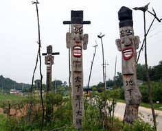 Jangseung, Korea: The Jangseung is a wooden pole (though sometimes made of stone) with a face carved near the top. They would normally be placed near the edges of villages to mark the village boundary and frighten evil spirits away from the village. Villagers would also pray to them to prevent calamity and bring a bountiful harvest.