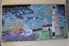 "20""x30"" stained glass and ocean rock mosaic designed to catch the light with irridescents scattered through the sea and light from the lighthouse to catch your eye and dance with movement."
