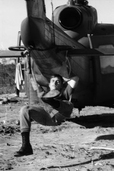 Sp5 Christopher H.Miller of Cocoa Beach,Fla.,gets rest in hammock slung under tail boom of Huey at Landing Zone Jamie,S Vietnam,October 1969.Choppers bringing Blue Platoon,C Troop,1st Sqdn,9th Cav,1st Air Cav Div troops to LZ Jamie,from where they would go on to search for source of enemy radio signals detected in area about 50 miles northwest of Saigon.They eventually discovered company-sized,23-bunker complex that had recently been vacated. (Joe Kamalick/Stars and Stripes)