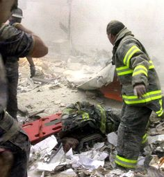 Firefighter Kevin Shea of Ladder 35 lies semi conscious in debris field with Firefighter Ritchie Nogan of 113 standing over him. Shea was the only survivor of his unit. He was carried out by Nogan, two EMS workers and photographer Todd Maisel. (Photo by Todd Maisel/NY Daily News Archive via Getty Images)