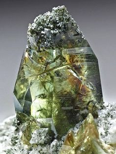 Titanite (Sphene) from Austria.  Sphere ranges in color from green through yellow to brown.  Cut properly, sphene gems can yield impressive flashes of fire.
