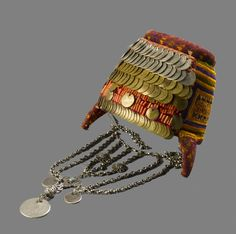 The Bethlehem headdress, Shatweh, whose front is covered with rows of coins, beads and coral was worn by married women of three neighboring villages, Bethlehem, Beit Jala and Beit Sahur | Unmarried women wore instead, a small circular embroidered cap (taqiyyeh) similar to the one worn in Jerusalem. Nineteenth century shatwehs were low and wide in shape, sparsely embroidered, and with few silver coins. In the 1920s, shatwehs became narrower but higher.