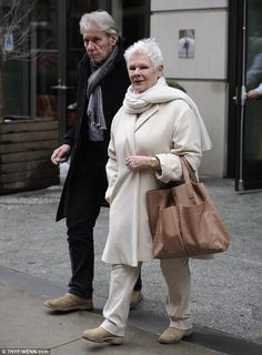 Out and about: Dame Judi Dench wears a cream and white ensemble as she and her boyfriend D...