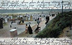 Hacia 1905  los alemanes ya estaban convencidos de la excelente influencia terapéutica de los baños de mar. Por entonces veraneaban en la estrecha franja costera que Alemania tiene en el Norte. Uno de los destinos favoritos de los veraneantes de entonces eran las islas de Frisia Oriental, como la de la postal. Tanto el deseo de mantener la tez blanca (¡!) como los fuertes vientos de la zona obligaban a refugiarse en estas bonitas cabinas de mimbre y tela. Eran otros tiempos... y otros…