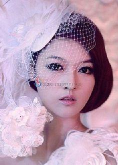 Chapeau avec voile pour mariée décoré de plume et de fleur