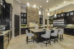The open gourmet kitchen is designed with an easy workflow, as well as to be friendly for family and entertaining. The space is grounded by neutral tiles, and black cabinets are paired with soft tan countertops. Stacked stone creates a focal wall and range above the stove, while the large center island is surrounded by light gray barstools for eating.