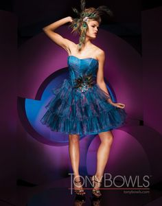 Strapless organza short A-line dress with boned pleated bodice, Basque waistline with offset hand-beaded peacock feather accent, tiered and pleated ruffle skirt. Detachable straps included.