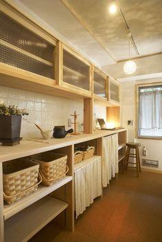キッチンの壁面に造作の食器棚を設置。吊戸棚は引き戸でガラス扉に。
