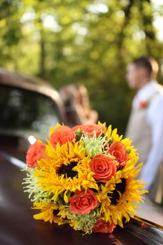 I really like this bouquet with sunflowers... I would want the other flowers to be yellow/orange gerbera daisies & white daisies.  Orange/red dahlias would be pretty too.