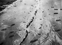 Thirteen ships deliberately scuttled to form a breakwater for invasion vessels landing on the Normandy beachhead lie in line off the beach shielding the ships in shore. The artificial harbor installation was prefabricated and towed across the Channel in 1944