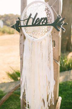 dream catcher chair decor - photo by Vis Photography http://ruffledblog.com/handcrafted-boho-woodsy-wedding #chairdecor #weddingideas #bohemianwedding