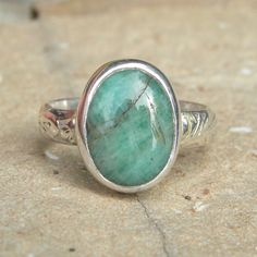 This is a rather simple sterling silver ring, with an oval, bezel set, opaque emerald cabochon.    The color is bluish green with brown veins.