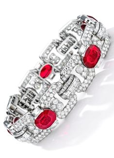 An Important Art Deco Ruby and Diamond Bracelet, Cartier, Paris, Circa 1920. Designed as a band of five oval rubies, each flanked with baguette diamonds, joined by single-, old European- and emerald-cut diamond links, mounted in platinum and 18 karat white gold, signed and numbered. #Cartier #ArtDeco #bracelet