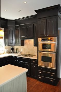 Paint the soffits the same color as the cabinets. Add molding between the soffits and cabinets and crown molding at the ceiling to make them look taller and custom built.