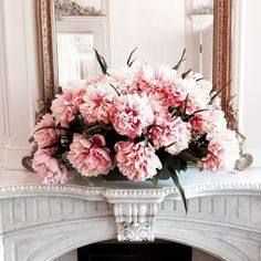 Gorgeous florals in pink on white mantel.