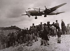 70 YEARS OF THE LUFTBRÜCKE 1948 - 2018  Berlin´s Neukölln children watching from a pile of rubble an American transport Douglas C-54 in her final approach to landing at Flughafen Tempelhof.  [Photo by Henry Ries / © NYT; Deutsches Historisches Museum Inventarnr.].