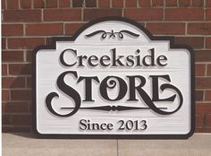 Creekside Store carved sign with carved background and raised letters.  Picture taken at our company before being packed and shipped to our client.