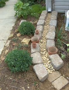 Making a dry creek bed for downspout. If you're tired of all of your mulch washing away every time it rains, rock is the answer. You don't have to border it but you can if you want.