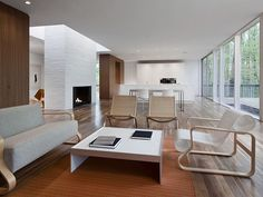 I love how minimal this room is.  Love the wall of windows across from the large, very simple fireplace.  Love the furniture.  Love, love, love.