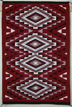 Hand woven Ganado Red rug by Helen Benally (Navajo) Helen Benally is 88 years old. A traditional Ganado rug always should have a red background. The central design motif is usually based on a single or double diamond pattern and the edges are typically embellished with geometric details. Ganado rugs are named for the town of Ganado where John Hubbell founded his trading post in 1878 and popularized the style in catalogs to buyers in the eastern United States.