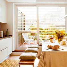 Cocina con salida a la terraza, mesa de comedor, banco con cojines y venecianas