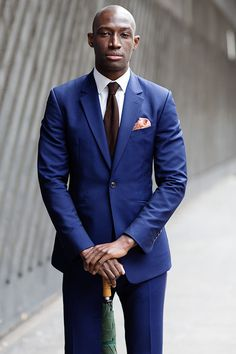 A trendy autumn look: indigo blue suit, paired with crisp white shirt and chocolate brown silk-knit tie. Notice the peach colored pocket square adding nice contrast and pop.