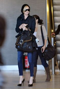 """Charlize Theron Oversized SatchelCharlize carries the functional-chic """"Saddle Bag"""" to fit all of her travel needs.  Brand: Christian Dior"""