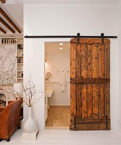 Farmhouse style sliding barn door leading to master bath. I've wanted to do this in the extra bedroom downstairs to separate 2 areas, but how to hang it from a flat ceiling??
