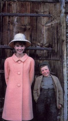 Audrey Hepburn photographed with a little boy by Howell Conant for a fashion editorial (for the American LIFE Magazine, edition of May 1962, but this same photo was not published), at a farm near her house in Bürgenstock (Switzerland), in February 1962.
