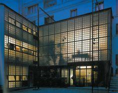 Pierre Chareau - Maison de verre - 1928 à Paris. espace total, dont la façade sur cour est complètement vitrée : une structure métallique tramée soutient des panneaux en pavés de verre. Tandis que les chambres s'isolent par des portes-placards, en bois ou métal, qui coulissent ou pivotent. La structure (poutres et poutrelles en acier), les canalisations et conduits restent visibles et participent à l'architecture, transformant ainsi les éléments utilitaires de la maison en éléments…