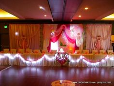 Cinderella Theme Quinceanera. Fairytale  Castle Decor.  Ceiling draped with shimmering fabric.  Satin, chiffon and painted murals created a stunning backdrop.  Floral centerpiece with custom lighted jeweled carriage.  Dance floor monogram. Revolving decor. Fairytale themed video projection on ballroom walls.  Affordable Event Production.  You won't know unless you call. Our prices our listed online! www.trightymite.com