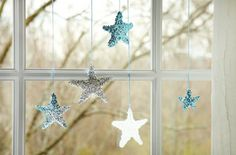 Glitter stars, easy and cheap to make and  would really shimmer with white lights lining the perimeter of the window.