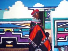 Ndebele housewife in front of a typically colorful Ndebele home.