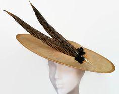 Pamela dorada y negra. Elegante pamela dorada de sinamay adornada con dos plumas de faisan doradas sujetas con decoración hecha de bolas negras.  La