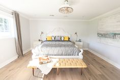 Master bedroom with yellow tufted mid century style bench - as featured on 'Rafterhouse' pilot episode on HGTV.
