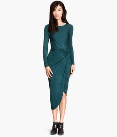 Knee-length dress in jersey with wrapover knot detail at one side. Long sleeves and asymmetric hem.
