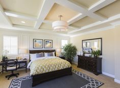 This bedroom features a beautiful coffered ceiling and paneled walls.  The mustard yellow bedding draws out the yellow undertones of the walls and the artwork hanging above the bed.