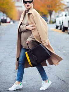 A neutral sweater is paired with a camel coat, jeans, sneakers, and a colorblock leather tote