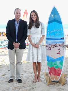 Catherine, Duchess of Cambridge and Prince William, Duke of Cambridge pose with a surfboard they were given as they attend a lifesaving event on Manley Beach on April 18, 2014 in Sydney, Australia