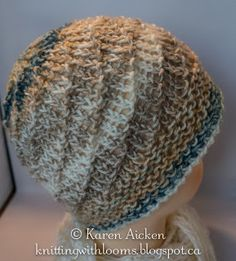 Lightweight Spiral Hat: Garter stitch brim, then switched to Spiral Hat pattern. Because loom had an odd number of pegs, E-wrap 4 pegs and purl one all the way around. Then start the next row on that last, unwrapped peg and that gives you the spiral pattern. The purl stitch moves one peg over every row without having to do much counting or peg marking.