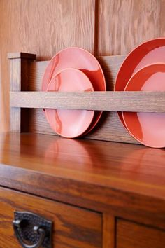 Pumpkin-colored place settings stored on display bring out reddish undertones in an oak sideboard.