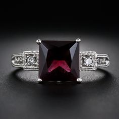 Vintage Style Garnet and Diamond Ring. Vintage Style Garnet and Diamond Ring. This striking and distinctive ring features a deep burgundy color scissor-cut garnet weighing 2.75 carats. The gemstone is tastefully presented in a bright white gold mounting enlivened with eight tiny full-cut diamonds set delicately milgrained settings. Recently produced with vintage design flourishes.
