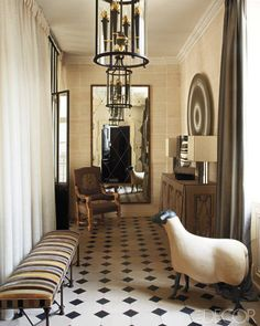 Gilbert Poillerat lanterns and a sheep sculpture by Francois-Xavier Lalanne in hallway designed by Jean-Louis Deniot.